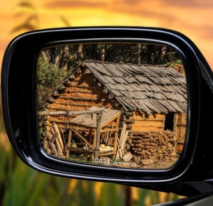 Old log cabin in rear view mirror