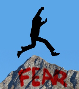 Overcoming fear, man jumping over a rock of fear