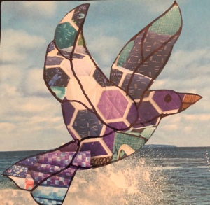Quilted paper art bird flying above the sea