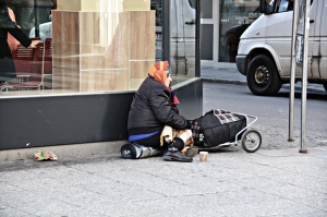 Homeless women sitting alone on a city sidewalk