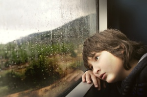 Person in thought, dreaming inside, beside a window covered in raindrops