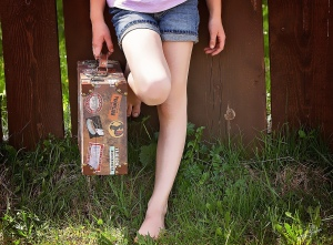 Girl barefoot with suitcase