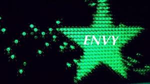 Green star in night sky symbolizes Envy