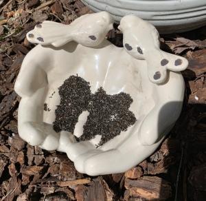 White ceramic hands holding birdseed