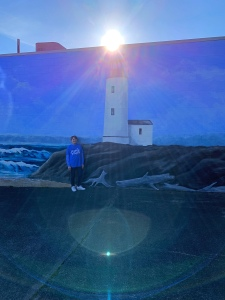 Me standing by a lighthouse mural