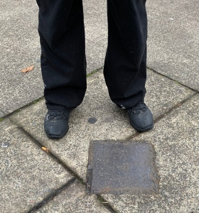 Legs and feet of a person standing in concrete sidewalk