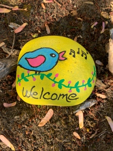 Painted rock says Welcome with bird singing