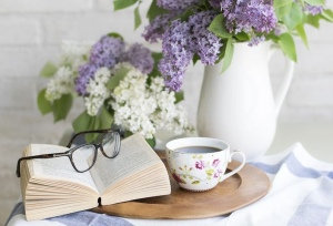 Open book with flowers and tea cup
