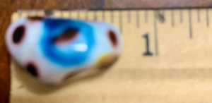 Tiny painted rock on a ruler