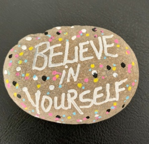 "Painted rock that says ""Believe in Yourself"""
